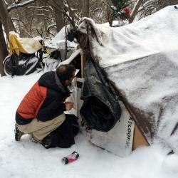 Staff member looking at a homeless camp.